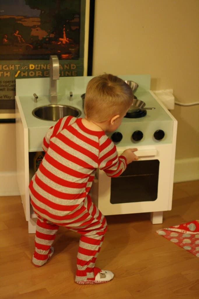 Toddler in pajamas laying with DIY IKEA hack play kitchen