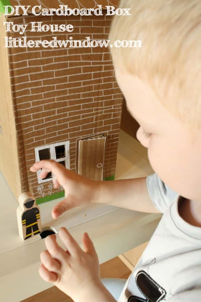 Little boy playing with a fireman figure next to the cardboard box house