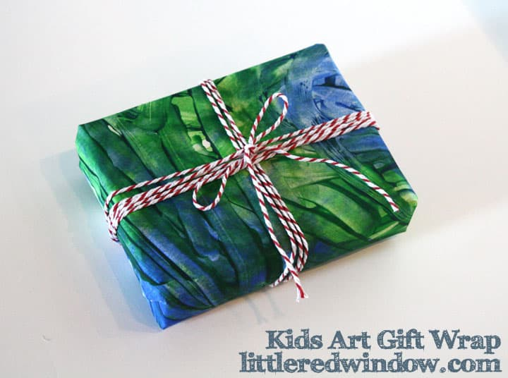 Small box wrapped with blue and green finger painted paper and tied with a red and white twine