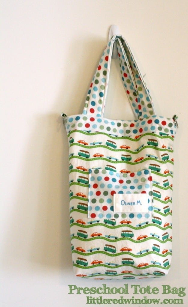 Handmade tote back with red and blue and green car and bus fabric in front of a white wall