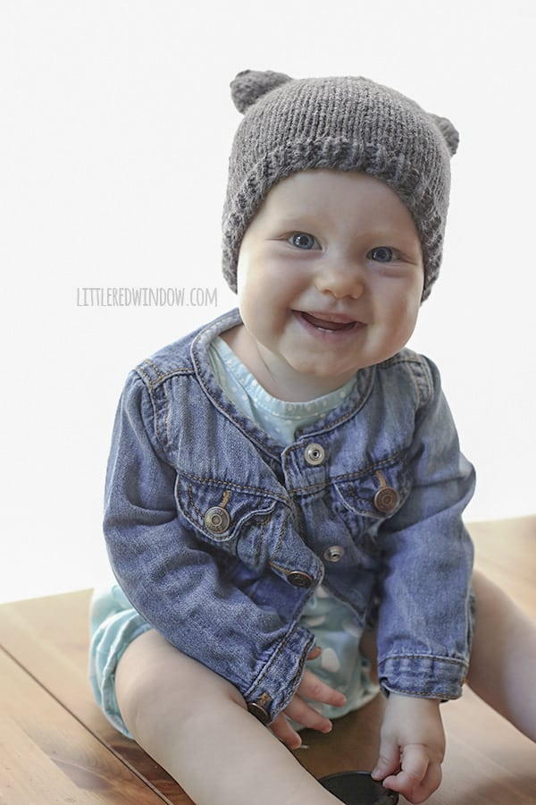 baby smiling and wearing a bear hat with ears and a jean jacket