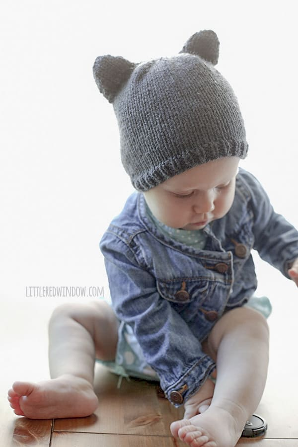Baby holding a lens cap and wearing a knit hat with bear ears