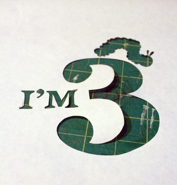"""Freezer Paper Stencil  of the words """"I'm 3"""" with a caterpillar shape on top of the 3"""