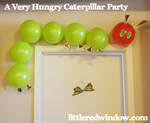 The very hungry caterpillar decoration made with green and red balloons and hung over a doorway