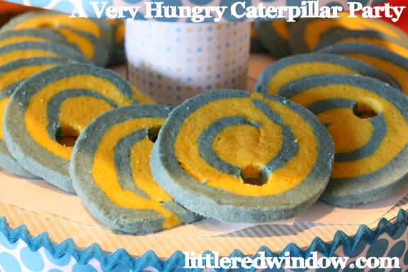 Yellow and blue sugar cookies with a swirl pattern on them and hole through as if eaten buy a caterpillar