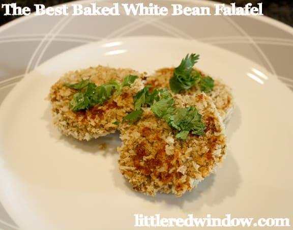 Three falafel with cilantro garnish on white plate