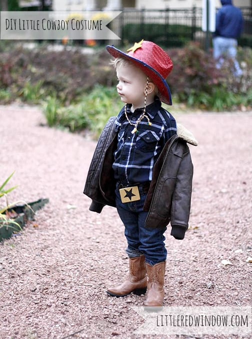 toddler wearing a cowboy costume in a park