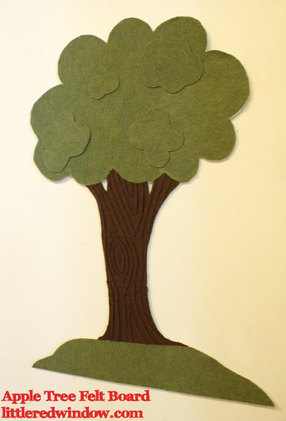 Green tree with brown bark made of felt on a flat white board