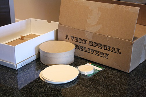 Two cardboard boxes, a round cardboard box with lid and flat wooden circles in large and small sizes on a counter