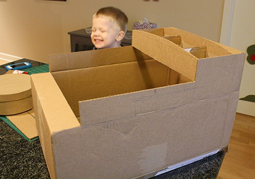 The top flaps of a cardboard box cut to make the shape of Thomas the Train with a toddler smiling in the background