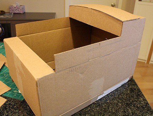 The top flaps of a cardboard box cut to make the shape of Thomas the Train, this time with a roof added to the back