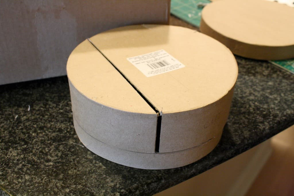 The base of a round cardboard box with about one third cut away