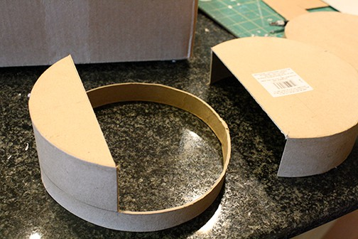 The round cardboard box with two thirds cut away to make the shape of the train's face