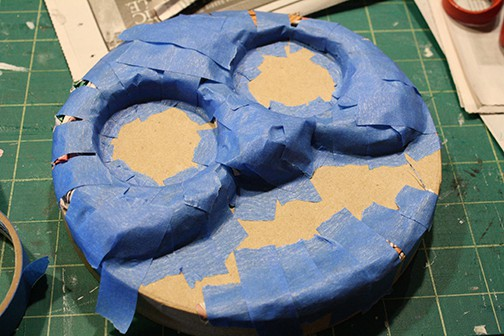 Lid of the round cardboard box with crumpled newspaper covered in blue painters tape to make the 3d shape of Thomas the train's face