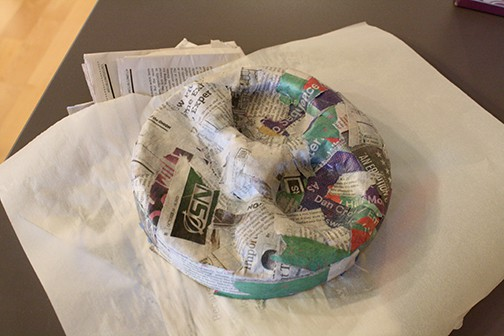 Lid of the round cardboard box with paper mache over it to make the 3d shape of Thomas the train's face