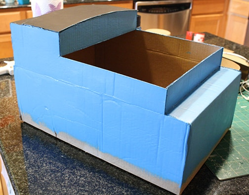 Cardboard box train shape painted blue with a black roof