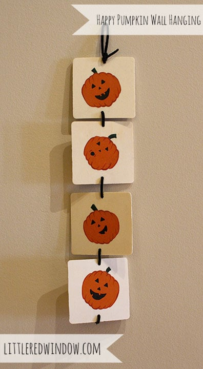 4 wooden squares with cute jack o lantern faces painted on them, hanging vertically