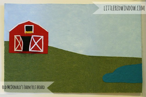 Felt board with a red barn on a green hill, blue sky and small pond