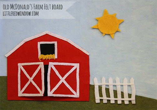 Closeup of felt red barn and white picket fence on a green hill with sun in the sky