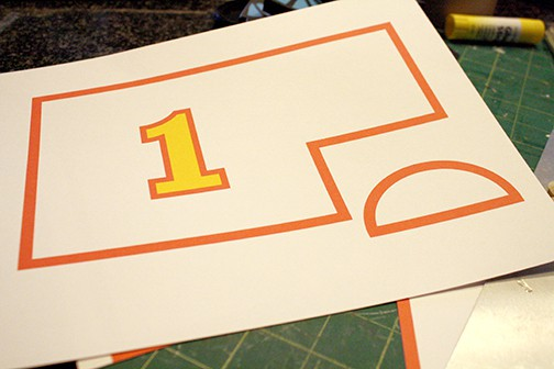 Piece of paper with decorative red rectangle and half circle and yellow number 1 to cut out and paste to the side of the train