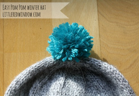 Closeup of gray hat with blue pom pom