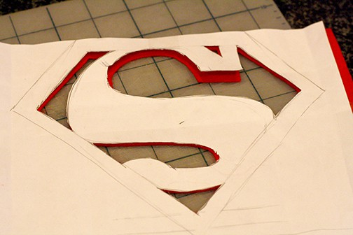 Paper Superman logo on top of red felt with the background areas cut out of the felt and paper