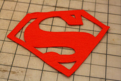 Red felt superman logo on a gray cutting mat