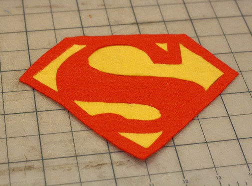 Red felt superman logo with the background areas filled with yellow felt