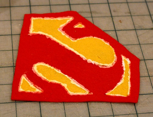 Back side of felt superman logo with fabric glue on it