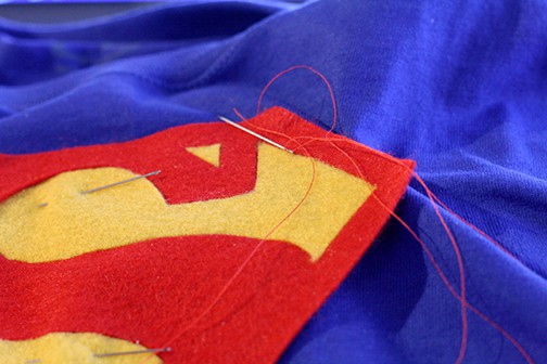 Felt superman logo being sewn onto a blue tshirt with a needle and red thread