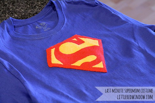 Blue tshirt laying flat with felt superman logo on it