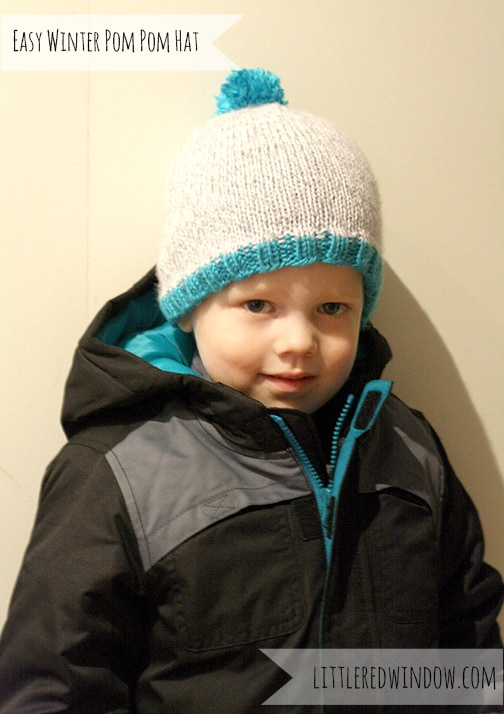 Little Boy wearing Gray knit hat with blue pom pom