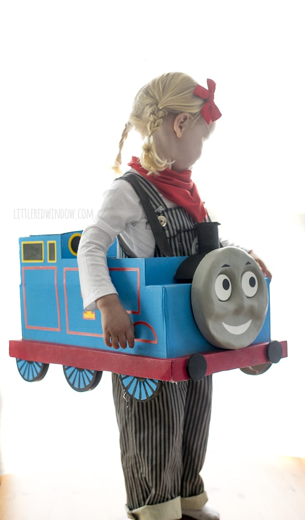 Little girl with braids wearing engineer costume and Thomas the Train box costume