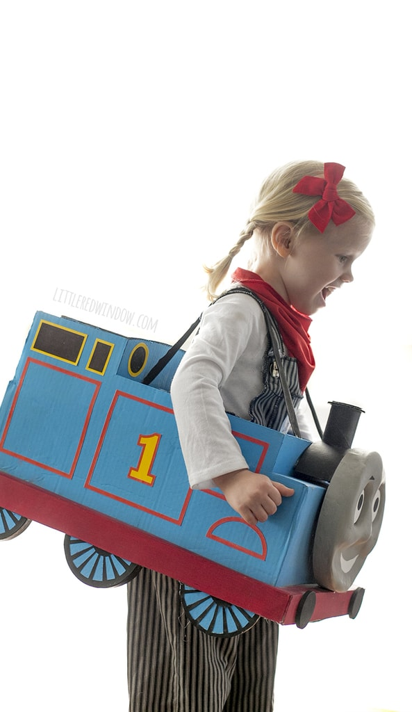 Side view of Little girl with braids wearing engineer costume and Thomas the Train box costume