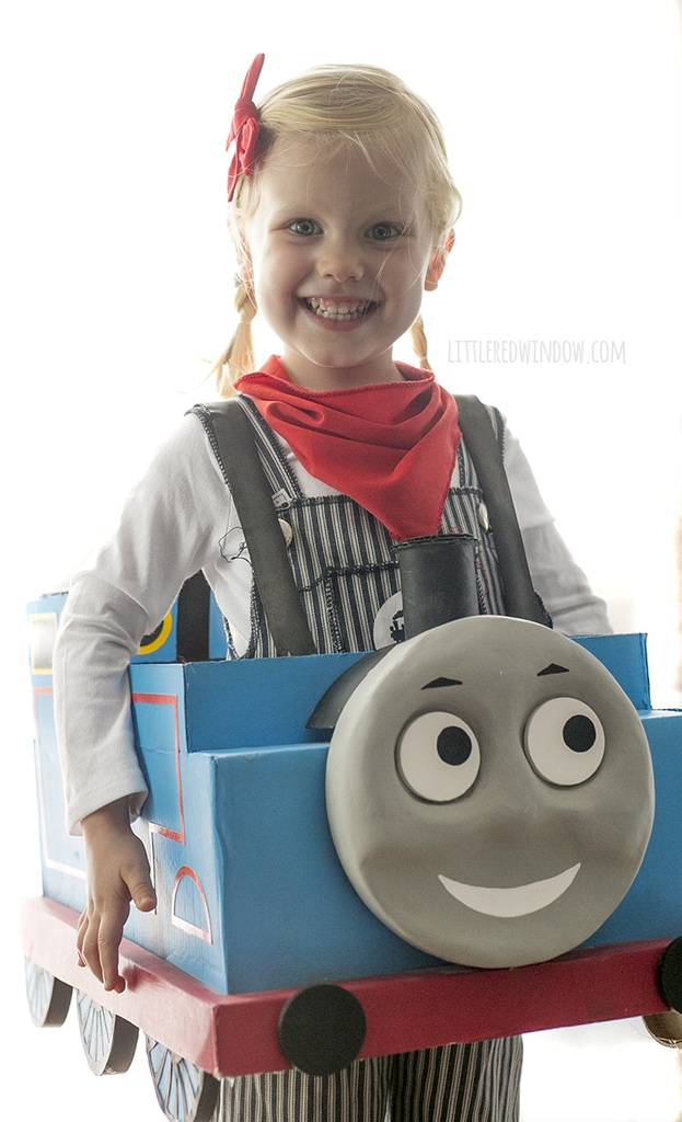 Smiling Little girl with braids wearing engineer costume and Thomas the Train box costume