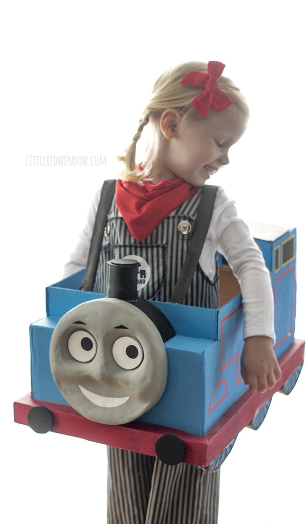 -Little girl with braids wearing engineer costume and Thomas the Train box costume looking over her shoulder