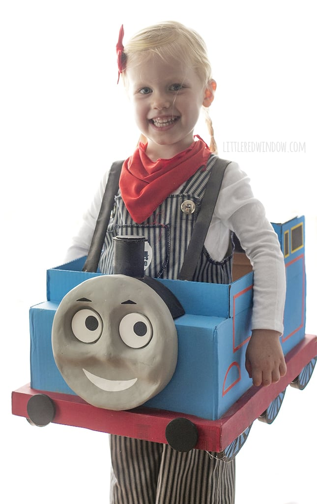 Smiling front view of Little girl with braids wearing engineer costume and Thomas the Train box costume