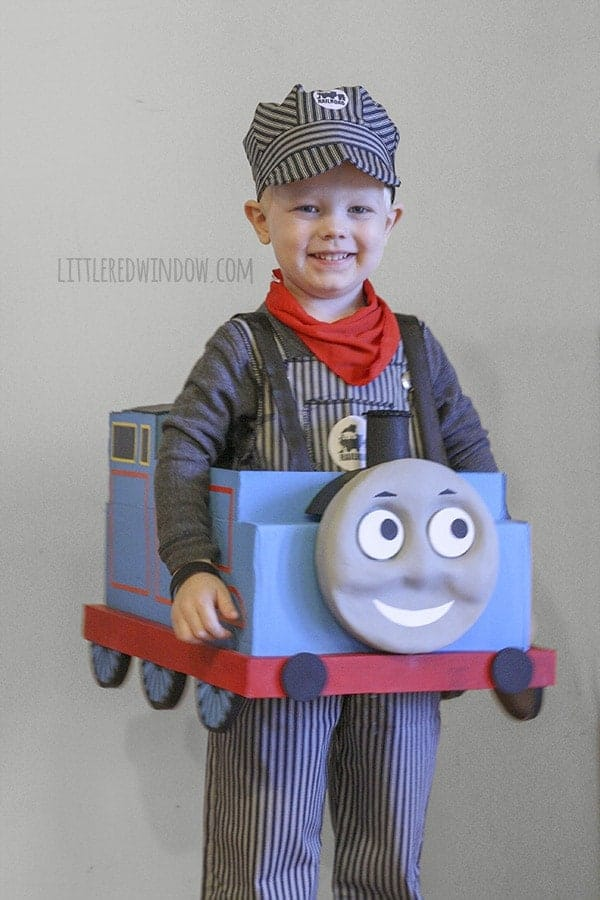 Smiling little boy wearing a train engineer costume and wearing the cardboard Thomas the Train costume!