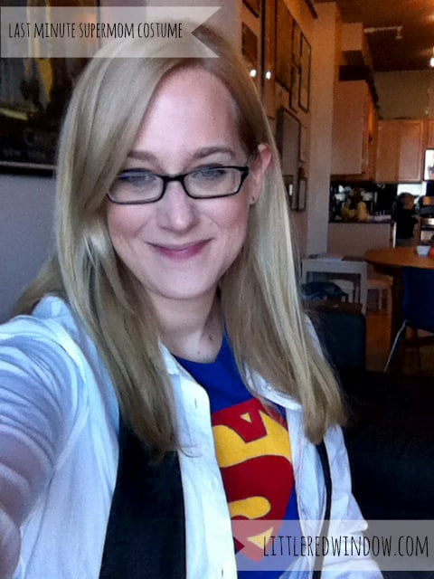 Woman with blond hair and black framed glasses wearing superman tshirt under white button up shirt