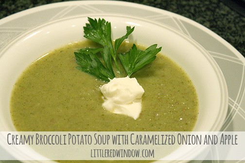 White bowl of green broccoli soup with sprig of parsley and dollop of sour cream