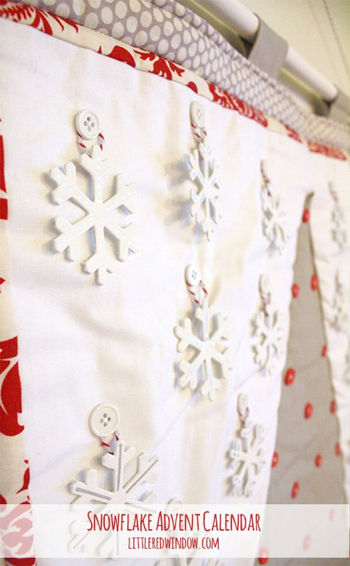 Closeup of white snowflake shapes hanging on buttons on the advent calendar