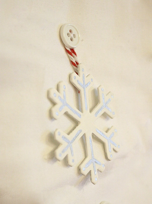 Closeup of handpainted snowflake shape, white with silver line design on it and red and white twine loop for hanging