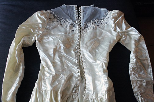 Bodice of a vintage wedding laying on a dark gray background