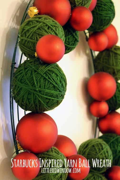 side view of Wreath made of green yarn balls and red Christmas ornaments hanging on a wall