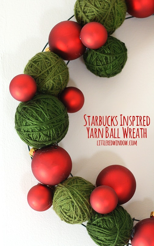 closeup of Wreath made of green yarn balls and red Christmas ornaments hanging on a wall