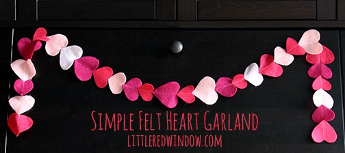 Simple pink and white heart garland hanging on a black cabinet
