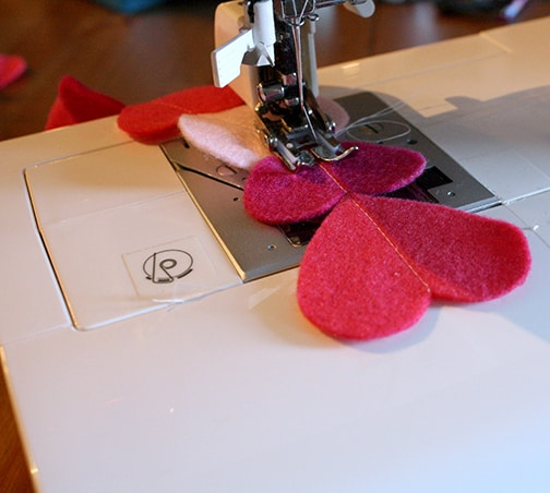Closeup of sewing machine sewing pink felt hearts in a line down their centers