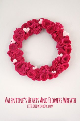 Wreath with hot pink felt flowers and light pink hearts hanging on a wall