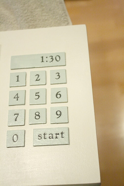 Microwave buttons glued in place in a grid on the microwave door