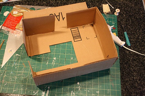 Strips of cardboard attached to sewing machine shape to make the sides